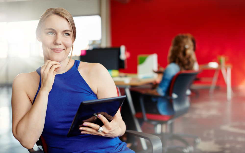 Confident female designer working on a digital tablet in red creative office space-1